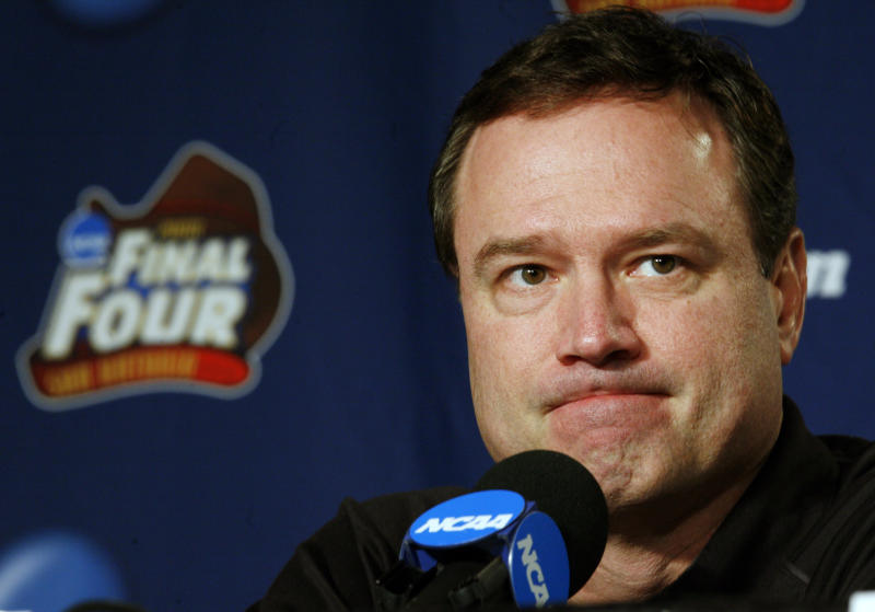 FILE - In this Sunday, April 6, 2008, file photo, Kansas head coach Bill Self listens to a question at a news conference before Monday's championship game against Memphis at the NCAA college basketball Final Four in San Antonio. The NCAA and networks across the sports dial have infused fans with a hoops fix by rebroadcasting epic NCAA Tournament games.  Coaches and players involved in those games are adding insight and a dash of humor by live tweeting during the replay. (AP Photo/Charlie Neibergall, File)