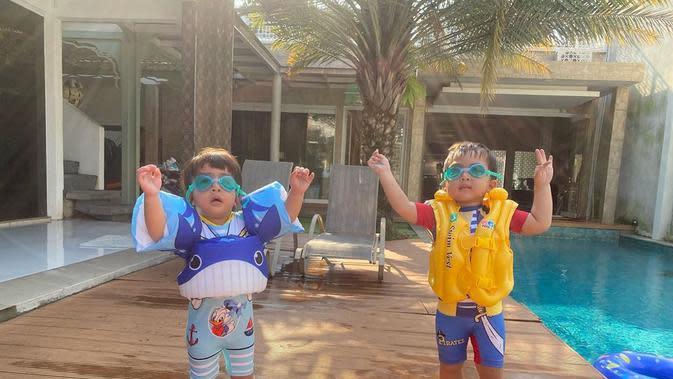 Terdapat juga kolam renang. Dua anak kembarnya mengenakan kaca mata renang dan plambung siap untuk berenang. Dibelakangnya juga tampak pohon kurma. Tapi, kata April belum pernah berbuah. (Youtube/Orami Indonesia)