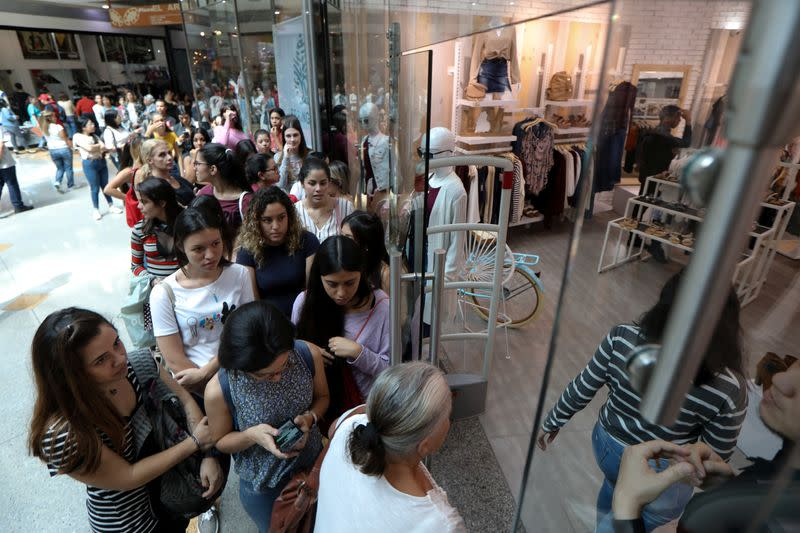 People stand in line outside a store at a mall during the Black Friday sales in Caracas