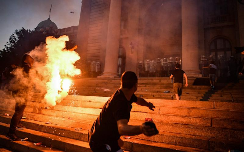 A protester prepares to throw a missile at police guarding Serbia's parliament on Wednesday as Belgrade was hit by a second night of rioting over a proposed renewed lockdown - ANDREJ ISAKOVIC/AFP