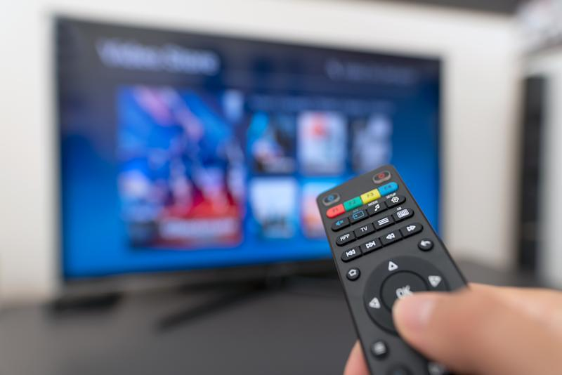 Multimedia streaming concept. Hand holding remote control. Video on demand