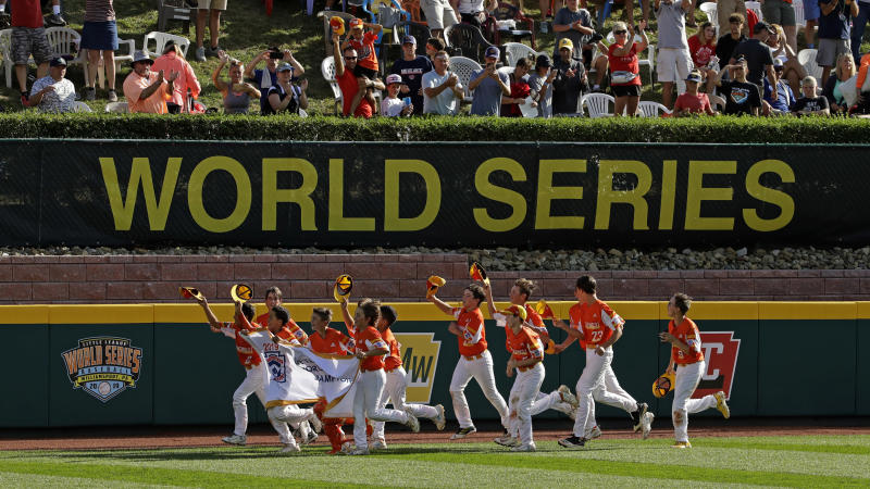 FILE - In this Sunday, Aug. 25, 2019, file photo, River Ridge, Louisiana, takes a victory lap around the field at Lamade Stadium after winning the Little League World Series Championship game against Curacao, 8-0, in South Williamsport, Pa. The 2020 Little League World Series and the championship tournaments in six other Little League divisions have been canceled because of the new coronavirus pandemic. (AP Photo/Gene J. Puskar, File)
