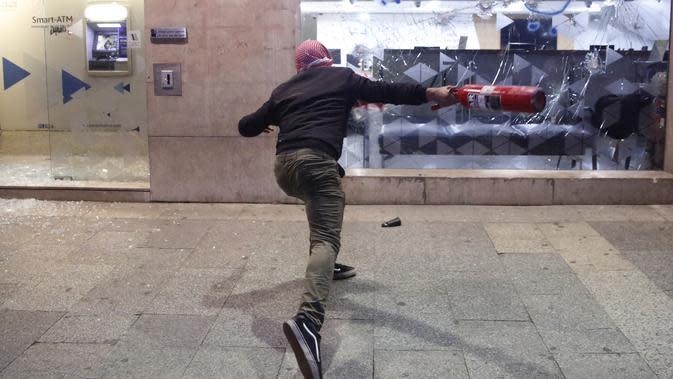 Demonstran antipemerintah merusak bank saat protes menentang elite penguasa di Beirut, Lebanon, Selasa (14/1/2020). Demonstran menganggap elite penguasa gagal mengatasi ekonomi yang menurun tajam. (AP Photo/Hussein Malla)
