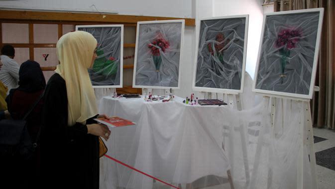 Seorang perempuan mengunjungi pameran seniman Palestina Kholoud al-Dasooqi di Gaza City, 11 Agustus 2020. Seniman Palestina asal Kota Khan Younis di Jalur Gaza itu menggelar pameran selama dua hari untuk mengungkap kekerasan terhadap perempuan melalui puluhan lukisan. (Xinhua/Rizek Abdeljawad)