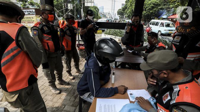 Petugas mendata warga pelanggar Pembatasan Sosial Berskala Besar (PSBB) yang terjaring razia masker di wilayah Tanah Abang, Jakarta, Senin (14/9/2020). Razia tersebut guna menekan kasus penyebaran COVID-19 di Jakarta pada masa PSBB. (Liputan6.com/Johan Tallo)