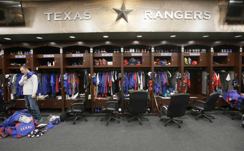 FILE - In this Oct. 11, 2016, file photo, Texas Rangers pitcher Sam Dyson, left, packs a bag in the locker room at the baseball park in Arlington, Texas. The NBA, NHL, Major League Baseball and Major League Soccer are closing access to locker rooms and clubhouses to all non-essential personnel in response to the coronavirus crisis, the leagues announced in a joint statement Monday, March 9, 2020. (AP Photo/LM Otero, File)