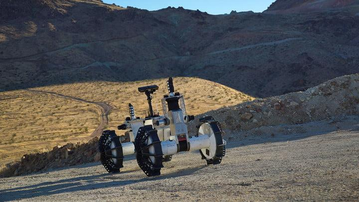 Terrain The DuAxel rover is seen here participating in field tests in the Mojave Desert. The four-wheeled rover is composed of two Axel robots. One part anchors itself in place while the other uses a tether to explore otherwise inaccessible terrain.