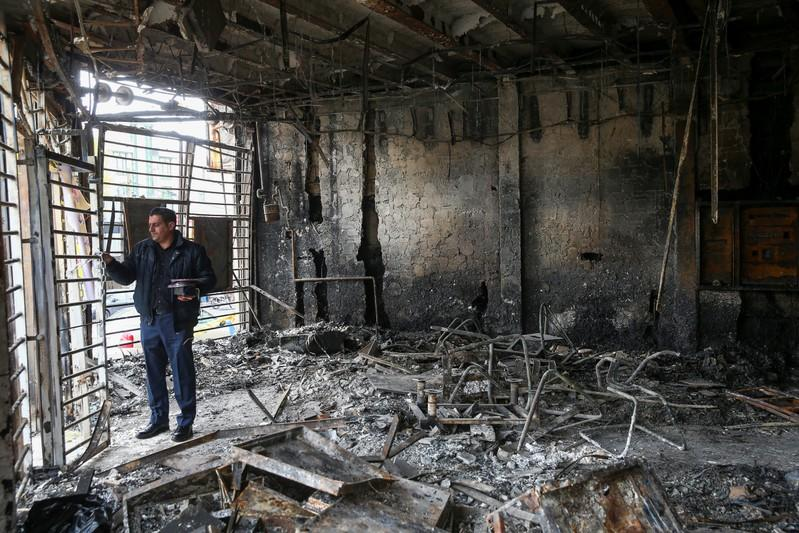 A man inspects the ruins of a bank after protests against increased fuel prices