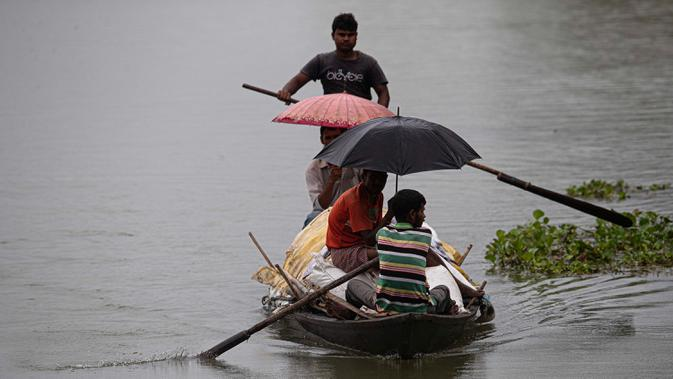 Penduduk desa melakukan perjalanan dengan perahu untuk mengungsi ketempat yang aman setelah banjir melanda kawasan distrik Morigaon di Assam, India (26/6/2020). Banjir merendam sejumlah wilayah yang dilalui Sungai Brahmaputra dan anak sungainya. (AP Photo/Anupam Nath)