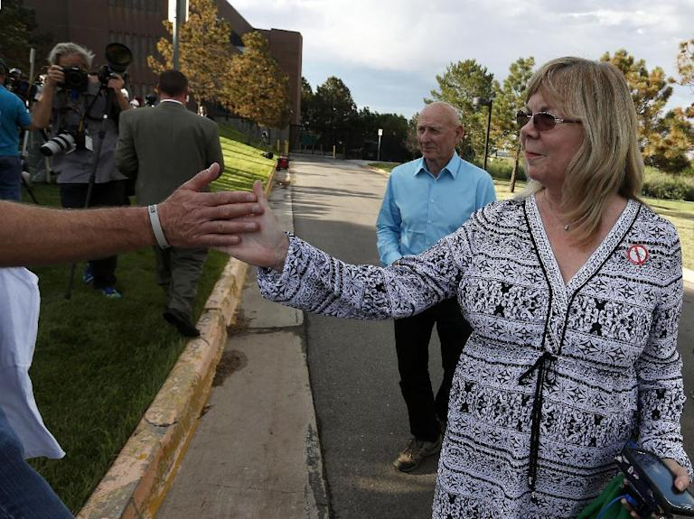 Sandy Phillips, right, and her husband Lonnie, who lost their daughter Jessica Ghawi in the 2012 Aurora movie theater massacre, gives a high-five to Tom Teves, who lost his son Alex in the attack, after attending the reading of the verdict in the trial of shooter James Holmes at the Arapahoe County District Court in Centennial, Colo., Thursday, July 16, 2015. (AP Photo/Brennan Linsley)