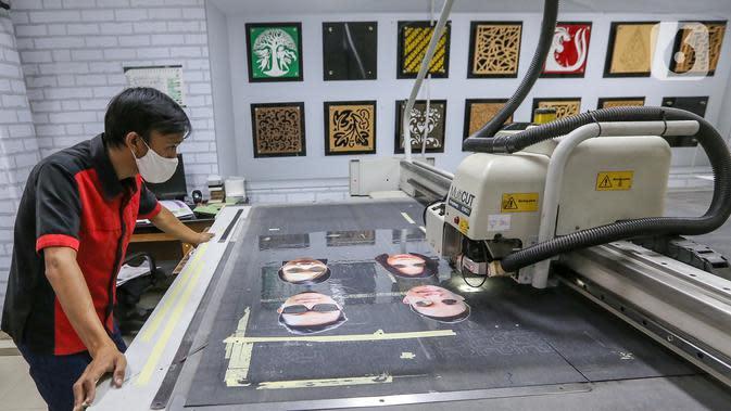 Karyawan melihat proses pemotongan mika pelindung wajah atau face shield karakter di percetakan Bintang Sempurna, Bendungan Hilir, Jakarta, Selasa (23/6/2020). Produksi face shield karakter yang hanya memakan waktu 5 menit dibanderol dengan harga Rp50 ribu per buah. (Liputan6.com/Fery Pradolo)