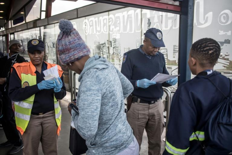 ID check: Papers are scrutinised at a bus station in the Johannesburg suburb of Soweto