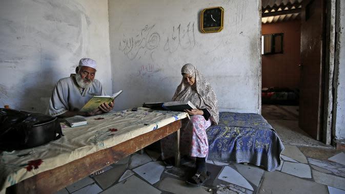 Seorang pria bersama istrinya membaca Al-Quran selama bulan suci Ramadan di Kota Gaza, Palestina, Jumat (1/5/2020). (MOHAMMED ABED/AFP)