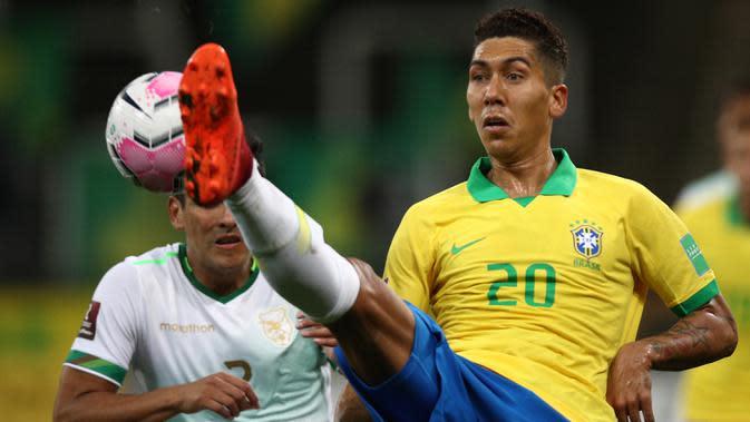 Penyerang Brasil, Roberto Firmino, berebut bola dengan bek Bolivia, Gabriel Valverde, pada laga kualifikasi Piala Dunia 2020 di Corinthians Arena, Sabtu (10/10/2020) pagi WIB. Brasil menang 5-0 atas Bolivia. (AFP/Buda Mendes/pool)