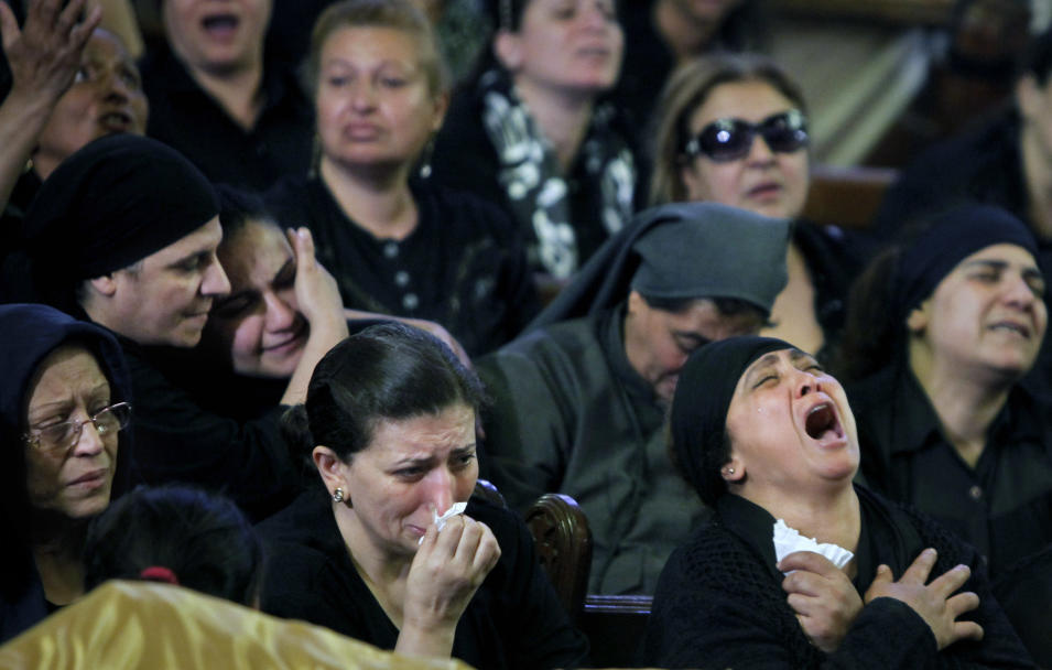 Egyptian Christians grieve during a funeral service at the Saint Mark Coptic cathedral in Cairo, Egypt, Sunday, April 7, 2013. Several Egyptians including 4 Christians and a Muslim were killed in sectarian clashes before dawn in Qalubiya, just outside of Cairo on Saturday, April 6, 2013. (AP Photo/Amr Nabil)