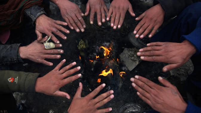 Sejumlah orang duduk di sekitar api untuk menghangatkan diri setelah hujan salju lebat di Kabul, Afghanistan, Selasa (14/1/2020). Warga Kabul terpaksa berhenti beraktivitas sebab suhu telah mencapai -15 derajat Celsius dan jalanan tertutup salju. (AP Photo/Rahmat Gul)