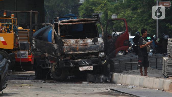 Kondisi mobil proyek yang hangus terbakar saat unjuk rasa menolak pengesahan Undang-Undang Cipta Kerja di kawasan Senen, Jakarta, Jumat (9/10/2020). Unjuk rasa tersebut berakhir ricuh dan mengakibatkan sejumlah fasilitas umum rusak. (Liputan6.com/Angga Yuniar)