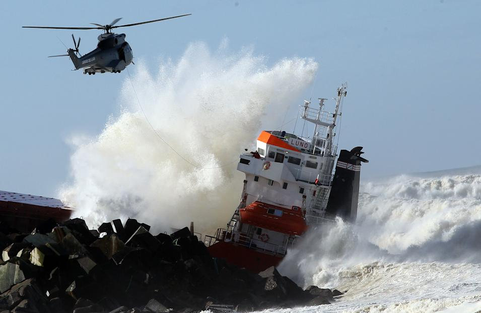 "A military helicopter flies over a Spanish cargo ship ""Luno"" that slammed into a jetty in choppy Atlantic Ocean waters and broke in two, off Anglet, southwestern France, Wednesday, Feb. 5, 2014. The ship had been heading to a nearby port to load up with cargo when its engine failed and the rough waves carried it into the jetty. (AP Photo/Bob Edme)"