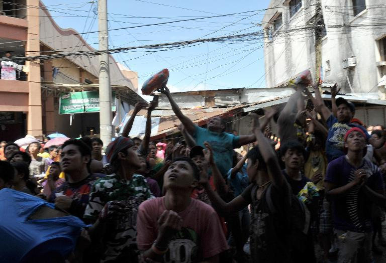 Residents scramble for looted goods in Tacloban, central Philippines, on November 10, 2013, after the city was devastated by Typhoon Haiyan