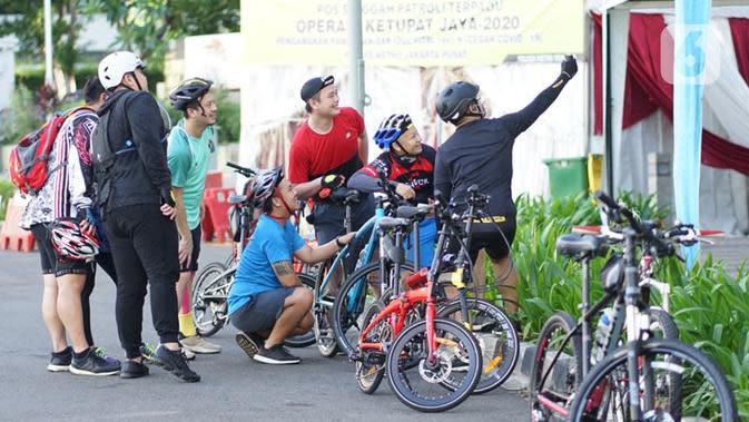 Sejumlah pesepeda berkumpul di kawasan Bundaran HI, Jakarta, Minggu (24/5/2020). Adanya PSBB serta Hari Raya Idul Fitri 1441 H dimanfaatkan sebagian warga untuk bersepeda di jalan protokol yang sepi dibanding hari biasa. (Liputan6.com/Immanuel Antonius)
