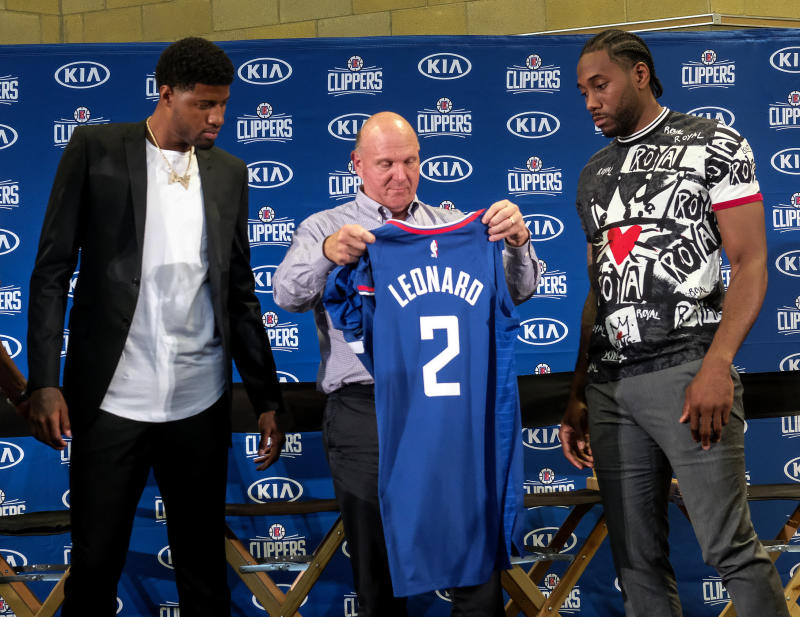 Los Angeles Clippers team chairman Steve Ballmer, center, presents a new team jersey to Kawhi Leonard, right, as Paul George looks on during a press conference in Los Angeles, Wednesday, July 24, 2019. Nearly three weeks after the native Southern California superstars shook up the NBA by teaming up with the Los Angeles Clippers, the dynamic duo makes its first public appearance. (AP Photo/Ringo H.W. Chiu)