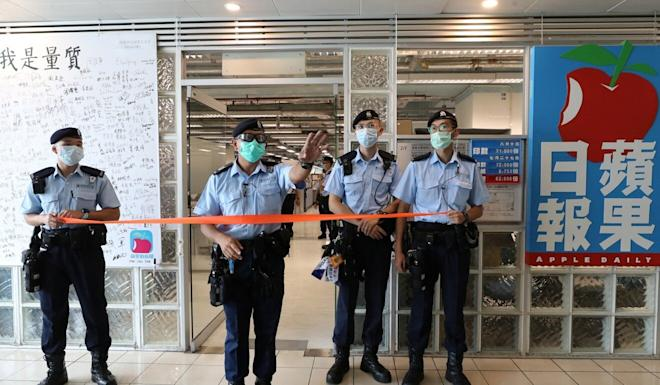 Police officers stand guard in front of the Apple Daily office in Hong Kong as it was raided on August 10. Photo: Reuters