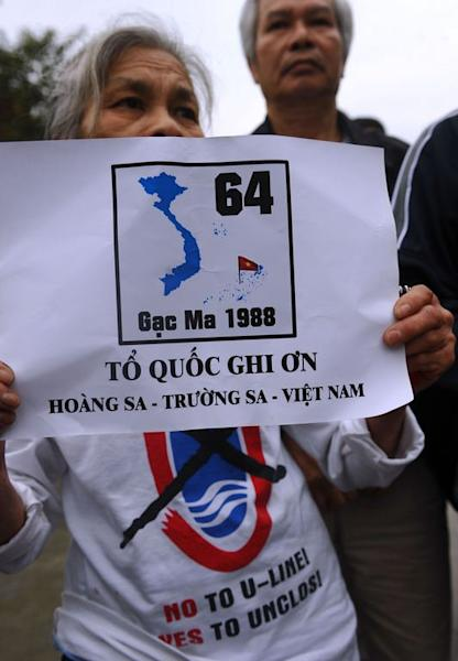 An elderly anti-China protester in Hanoi holds a poster remembering the 64 Vietnamese sailors killed March 14, 1988 during a Sino-Vietnam naval battle at Gac Ma island in the contested Spratly Islands