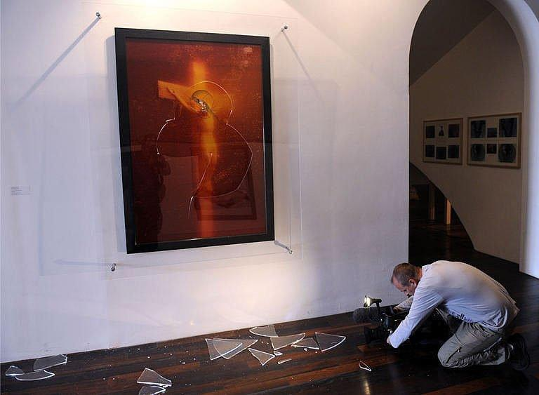 """Broken piece of glass from """"Immersion Piss Christ"""" are seen on the floor"""