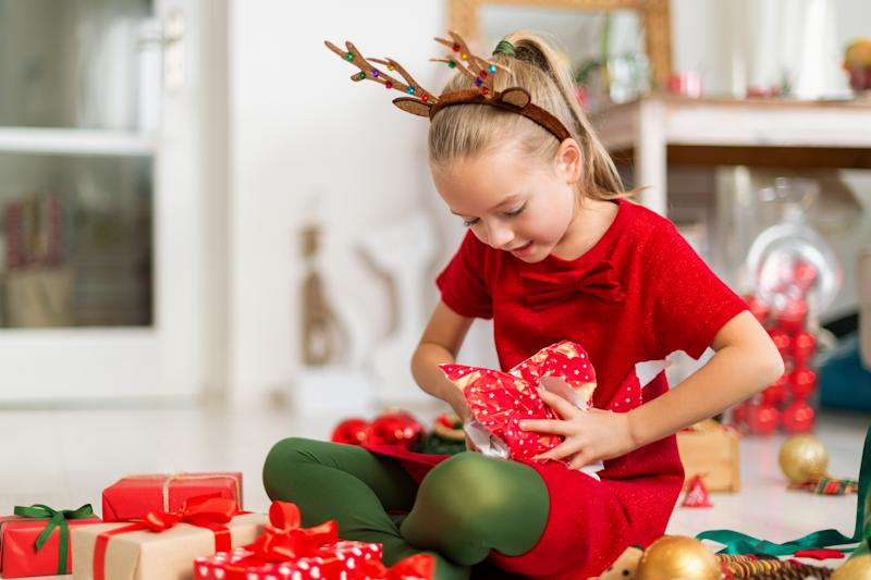Cute super excited young girl opening large red christmas present while sitting on living room floor. Candid family christmas time lifestyle background.