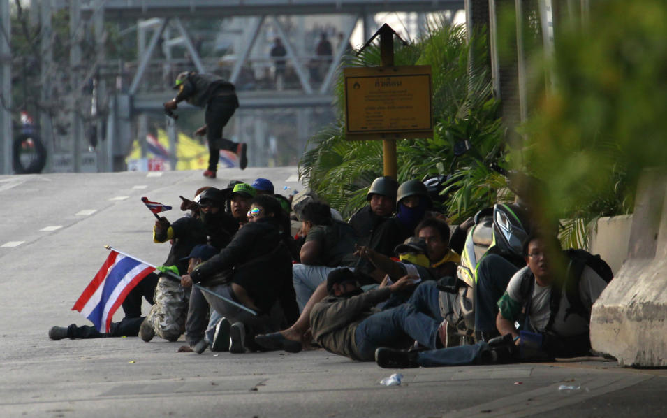 Anti-government protesters take cover on the street after their convoy of trucks was attacked during a clash with a pro-government armed group in Bangkok, Thailand Saturday, Feb. 1, 2014. Gunfire rang out at a major intersection in Thailand's capital on Saturday as clashes between protesters and government supporters erupted on the eve of tense nationwide elections. At least seven people are reported wounded, including an American photojournalist. (AP Photo/Wason Wanichakorn)