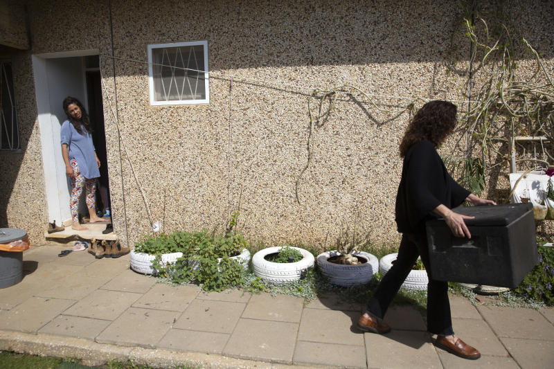 In this Monday, April 6, 2020 photo, emergency room doctor, Maayan Bacher, left, watches volunteer Einat Kedem leave after delivering a home-cooked meal, in the Israeli city of Raanana. More than 10,000 people have responded to Israeli Adi Karmon Scope's Facebook plea to help overworked health-care professionals on the frontline of the country's battle against the coronavirus pandemic. An army of volunteers is doing their grocery shopping, delivering home-cooked meals, babysitting for children and even walking pets. (AP Photo/Sebastian Scheiner)