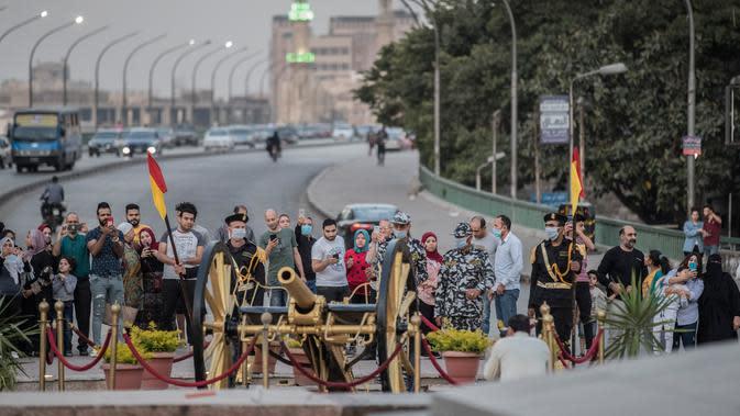 Pasukan keamanan Mesir mengenakan masker bersiap untuk menembakkan meriam Ramadan untuk menandai berbuka puasa di distrik Giza, Kairo, Senin (11/5/2020). Meriam tradisional tersebut selalu digunakan pada bulan suci Ramadan untuk mengumumkan iftar atau waktu berbuka puasa. (Khaled DESOUKI / AFP)