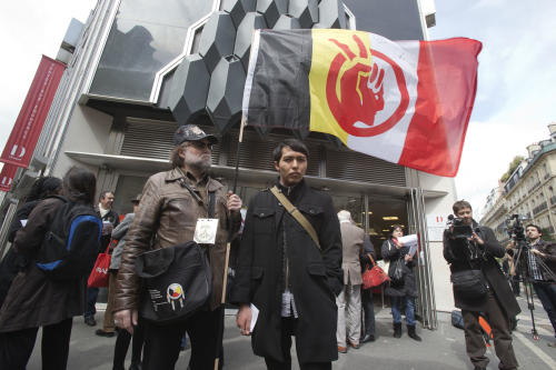 A French supporter of the Indian cause, who refused to give his name, left, holds a flag of the American Indian Movement and an American exchange student, member of the Arizona's Hopi tribe, Bo Lomahquahu, right, stand outside of the Druout's auction house to protest the auction of Native American Hopi tribe masks in Paris, Friday, April 12, 2013. A contested auction of dozens of Native American tribal masks went ahead Friday afternoon following a Paris court ruling, in spite of appeals for a delay by the Hopi tribe, its supporters including actor Robert Redford, and the U.S. government. (AP Photo/Michel Euler)