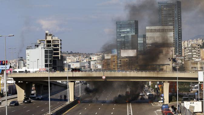 Demonstran antipemerintah membakar ban untuk memblokir jalan saat protes menentang elite penguasa di Kota Jal el-Dib, Lebanon, Selasa (14/1/2020). Demonstran menganggap elite penguasa gagal mengatasi ekonomi yang menurun tajam. (AP Photo/Bilal Hussein)