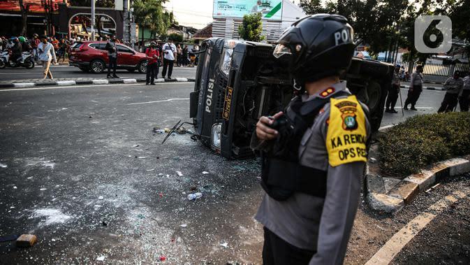 Polisi berdiri dekat sebuah mobil polisi yang dirusak massa saat bentrok di kawasan Pejompongan, Jakarta, Rabu (7/10/2020). (Liputan6.com/Faizal Fanani)