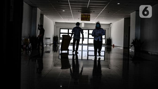 Petugas dengan alat pelindung diri membuang limbah dari Pusat Rawat Isolasi Khusus Mandiri di Stadion Patriot Candrabhaga, Bekasi, Rabu (23/9/2020). Dinas Kesehatan Bekasi menyiapkan 57 tempat tidur di rumah sakit darurat itu sebagai sarana isolasi mandiri pasien Covid-19. (merdeka.com/Iqbal Nugroho