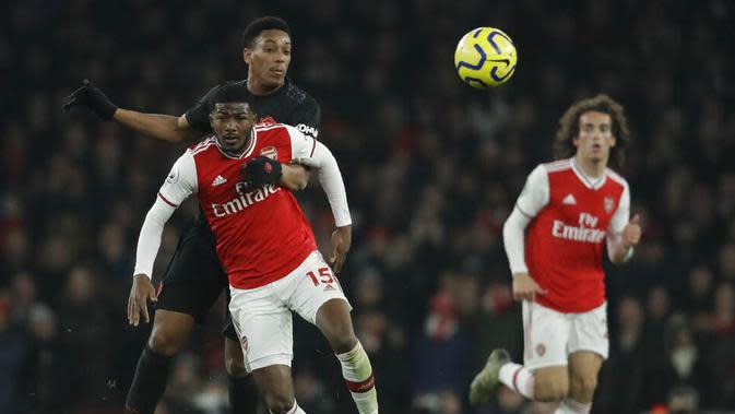 Pemain Arsenal, Ainsley Maitland-Niles, berebut bola dengan pemain Manchester United, Anthony Martial, pada laga Premier League di Stadion Emirates, Rabu (1/1/2020). Arsenal menang 2-0 atas Manchester United. (AP/Matt Dunham)