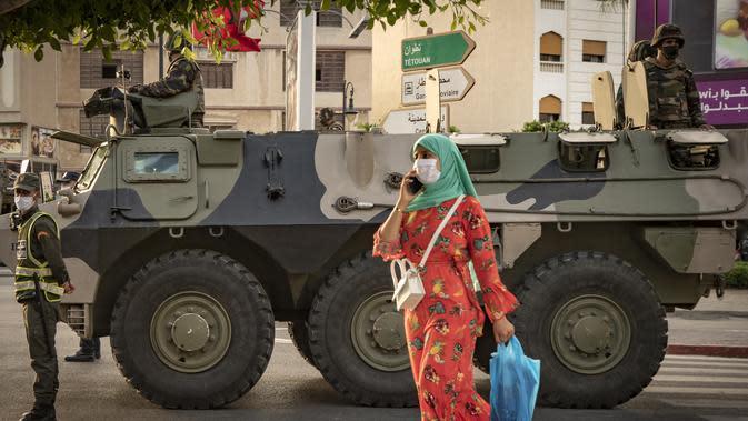 Seorang wanita berjalan saat tentara Maroko berpatroli di tengah wabah baru virus corona baru di kota Tangiers (11/8/2020). Tentara dikerahkan untuk meredam Lonjakan kasus Covid-19 di negara tersebut. (AFP/Fadel Senna)