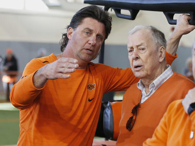 Oklahoma State head coach Mike Gundy, left, explains a drill to T. Boone Pickens, right, during an NCAA college football Pro Day in Stillwater, Okla., Thursday, March 15, 2018. (AP Photo/Sue Ogrocki)