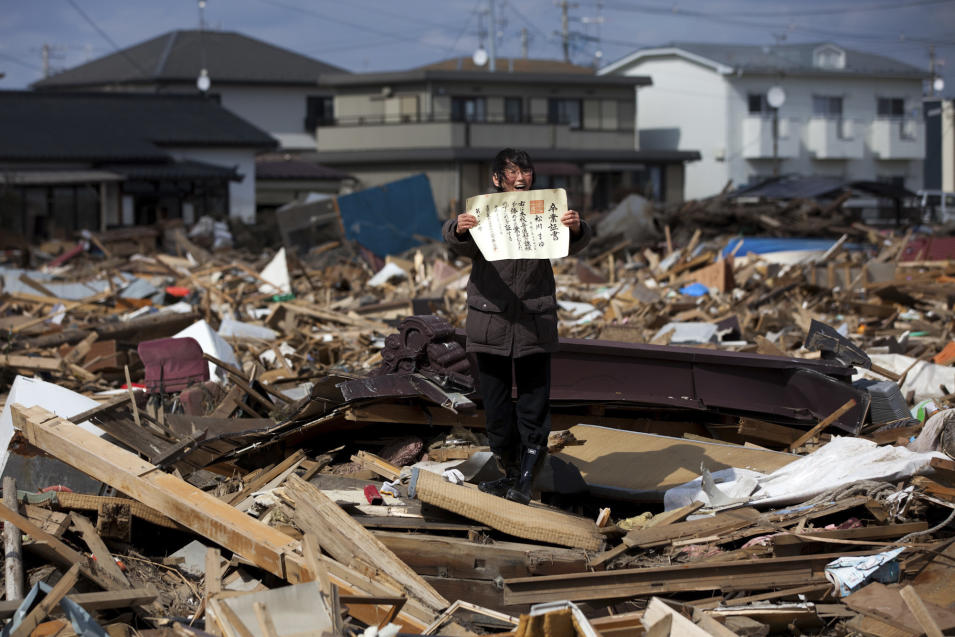 In this photo provided on Friday Feb. 10, 2012 by World Press Photo, the 1st prize People in the News Stories category of the 2012 World Press Photo Contest by Yasuyoshi Chiba, Japan, Agence France-Presse shows the aftermath of the tsunami in Japan, April 3, 2011. Chieko Matsukawa shows her daughter's graduation certificate as she finds it in the debris in Higashimatsushima city, Miyagi prefecture, Japan. (AP Photo/Yasuyoshi Chiba, AFP)
