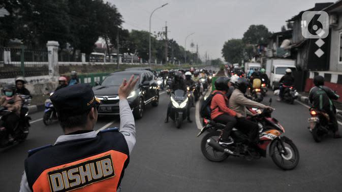 Petugas Dishub mengatur lalu lintas saat sebagian pengendara sepeda motor melawan arah ke jalan alternatif untuk menghindari kemacetan di Underpass Pasar Minggu, Jakarta, Kamis (12/3/2020). Kemacetan di Underpass Pasar Minggu semakin parah saat jam pulang kerja. (merdeka.com/Iqbal Nugroho)