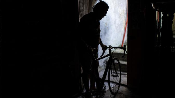 Raffaello Bianco, mekanik dan pecinta sepeda terlihat di pintu masuk bengkel mekaniknya di ruang bawah tanah apartemennya di Turin, Italia, 7 Juli 2020. Di antara banyak pesepeda amatir yang memintanya untuk memperbaiki sepeda, ada pengendara profesional seperti Fabio Fellini. (MARCO BERTORELLO/AFP)