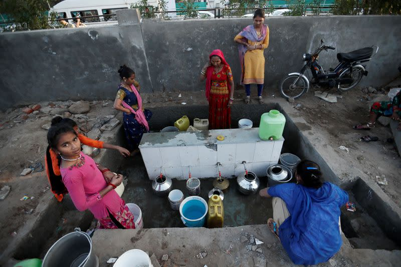 Women fill water from a tap in front of a wall constructed as part of beautification works for U.S. President Donald Trump's visit, in Ahmedabad
