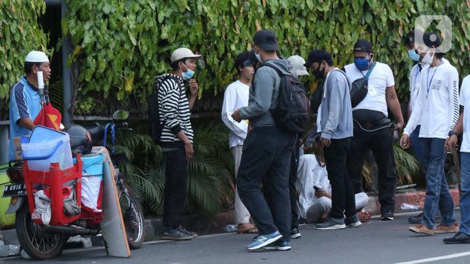 Polisi berpakaian kaus putih memeriksa sekelompok anak muda yang dicurigai terlibat kericuhan di kawasan Tugu Tani, Jakarta, Selasa (13/10/2020). Sejumlah pemuda diamankan polisi karena dicurigai terlibat kericuhan di kawasan Tugu Tani. (Liputan6.com/Helmi Fithriansyah)