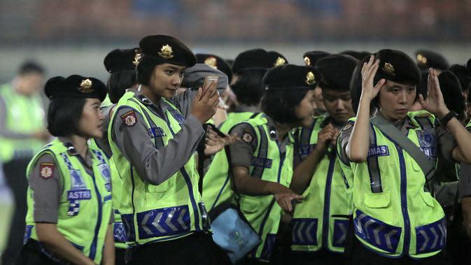 Polwan (Polisi Wanita) merapikan seragam sebelum pengarahan usai pengamanan di Stadion Si Jalak Harupat, Bandung, Minggu (25/10/2015). (Bola.com / Nicklas Hanoatubun)
