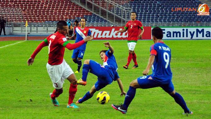 Pemain Timnas Indonesia Raphael Maitimo berusah keluar dari jagaan pemain Timnas Laos dalam Laga Piala AFF Suzuki 2012 Minggu 25 November 2012, di Stadion Bukit Jalil, Kuala Lumpur Malaysia. Pertandingan berakhir dengan Skor 2-2.