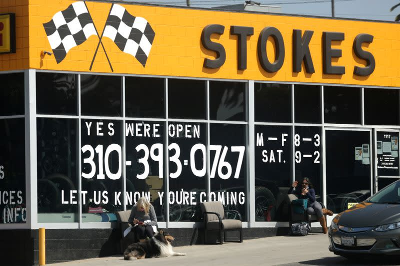 People wait outside a newly-reopened tire store, as the global outbreak of the coronavirus disease (COVID-19) continues, in Santa Monica