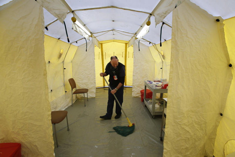 Steve Moody, director of nursing at Central Maine Medical Center, mops the floor of a tent outside the emergency entrance to the hospital where patients are tested for of the coronavirus Friday, March 13, 2020, in Lewiston, Maine. U.S. hospitals are setting up circus-like triage tents, calling doctors out of retirement, guarding their supplies of face masks and making plans to cancel elective surgery as they brace for an expected onslaught of coronavirus patients. (AP Photo/Robert F. Bukaty)