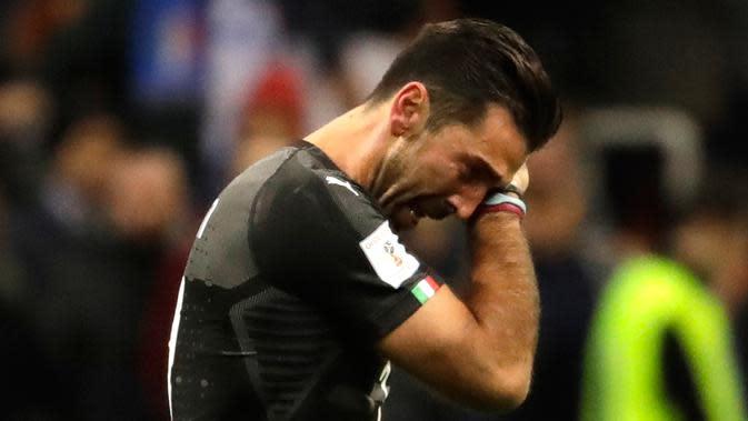 Kiper Italia, Gianluigi Buffon mengusap air matanya seusai menjamu Swedia pada playoff zona Eropa di Stadion San Siro, Selasa (14/11). Buffon tak kuasa menahan tangis setelah timnya gagal lolos ke Piala Dunia 2018. (AP/Luca Bruno)