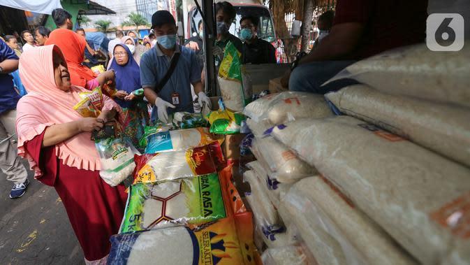 Warga membeli beras dan minyak goreng saat Operasi Pasar di Pasar Palmerah, Jakarta, Jumat (20/3/2020). Perum Bulog menjual gula pasir, beras dan minyak goreng dengan harga murah dan terjangkau yang tersebar di 35 titik pasar. (Liputan6.com/Fery Pradolo)